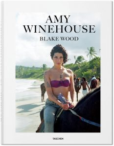 """Auf dem Foto ist das Cover des Bildbands """"Amy Winehouse by Blake Wood"""", erschienen im Taschen Verlag zu sehen. Am sitzt auf einem Pferd, tragt ein pinkes Bikini-Oberteil und eine Jeans und reitet barfuß am Plantation Beach in Saint Lucia. Das Foto stammt aus dem Jahr 2009."""