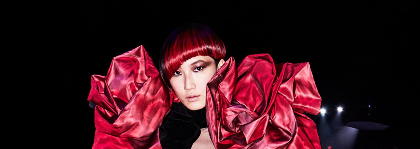 Auf dem Foto ist ein asiatisches Model zu sehen. Sie hat rote Haare und ihre Frisur bezeichnet man als Bob.