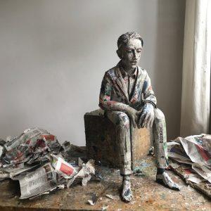 Auf dem Foto ist eine sitzende Figur aus Pappmacheé zu sehen. Es ist der Rohzustand von einem Werk von der Künstlerin und Bildhauerin Annette Meincke-Nagy.