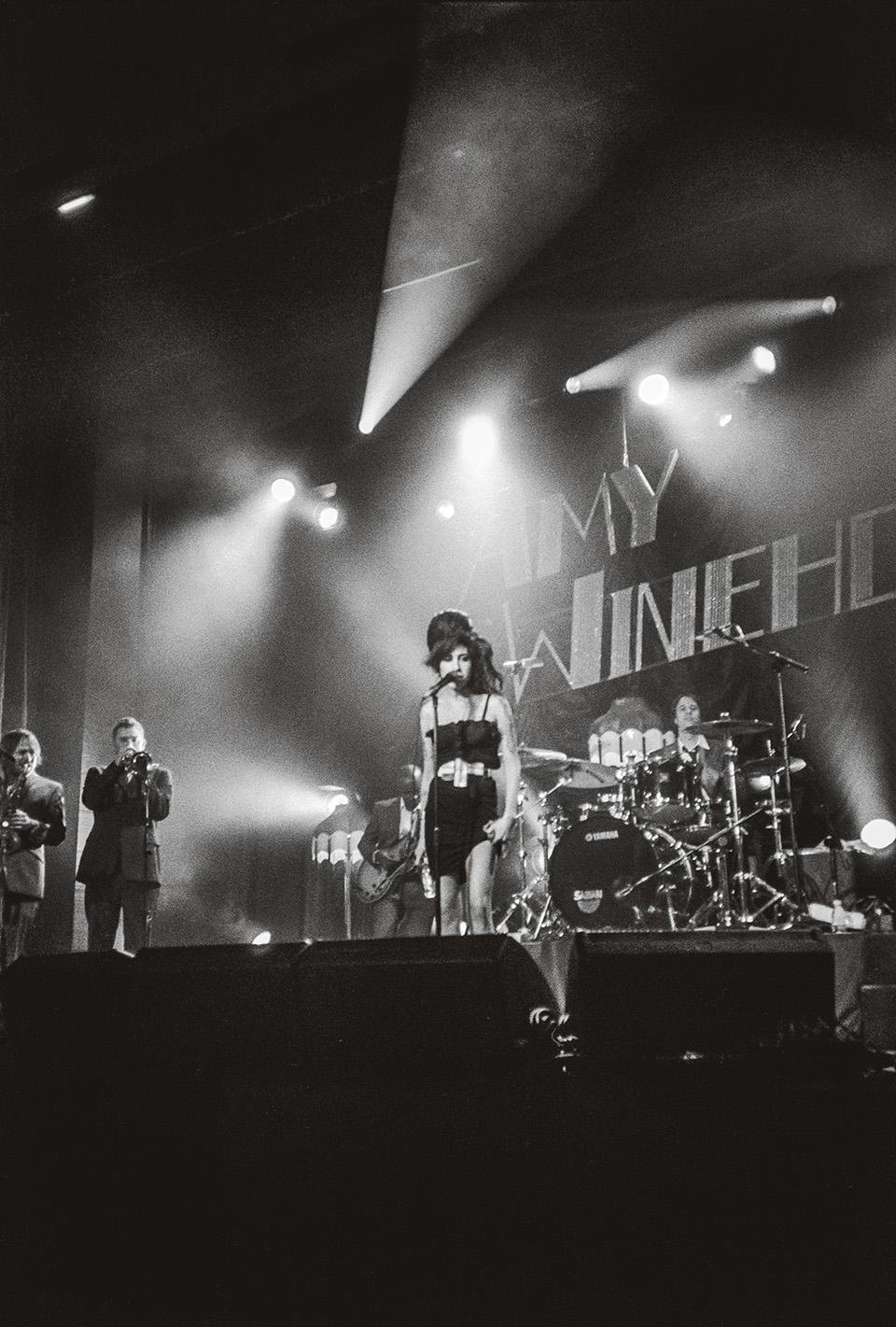 Amy Winehouse steht auf einer Bühne vor einem Mikrofon. Sie trägt ein schwarzes Minikleid. Hinter ihr ist ein riesiges Schlagzeug zu erkennen.