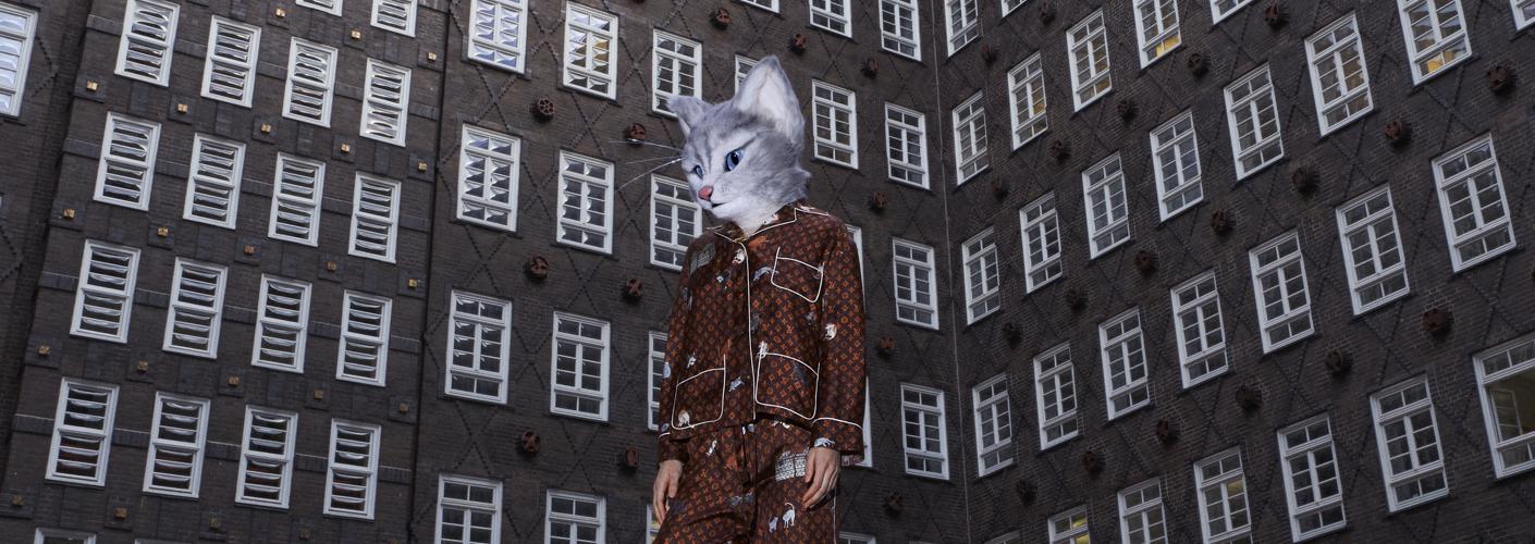 Auf dem Foto ist Miezekatze Pheline in einem Pyjama aus der Cruise Collection von Louis Vuitton x Grace Coddington zu sehen. Der Pyjama ist braun und bedruckt mit dem typischen orangefarbenen LV Monogram und Zeichnungen von Grace Goddington, die ihre Perserkatzen Pumpkin und Blanket abbilden. Pheline steht vor einem Gebäude mit vielen weißen Fenstern und rot-braunen Backsteinen.
