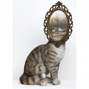 Auf dem Foto ist der Körper einer Katze zu sehen. Doch statt eines Kopfes hat sie ein ovales Bild mit Rahmen.