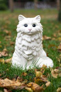 """Auf dem Foto ist eine weiße Katze aus Porzellan zu sehen. Es ist der Flyer zu der Ausstellung in der Galerie Affenfaust """"Katzen gehen immer noch"""""""