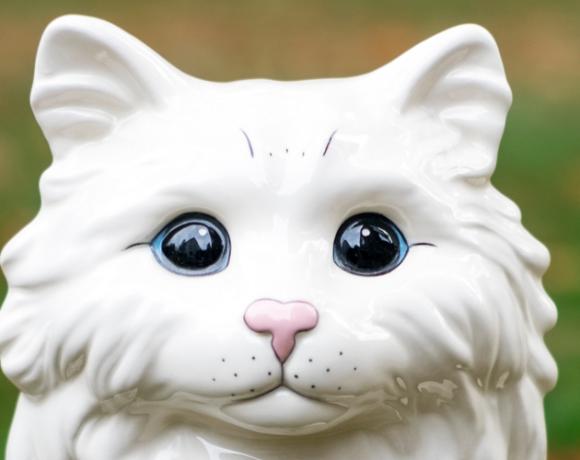 """Auf dem Foto ist ein weißer Katzenkof aus Porzellan zu sehen. Es ist der Flyer zu der Ausstellung in der Galerie Affenfaust """"Katzen gehen immer noch"""""""