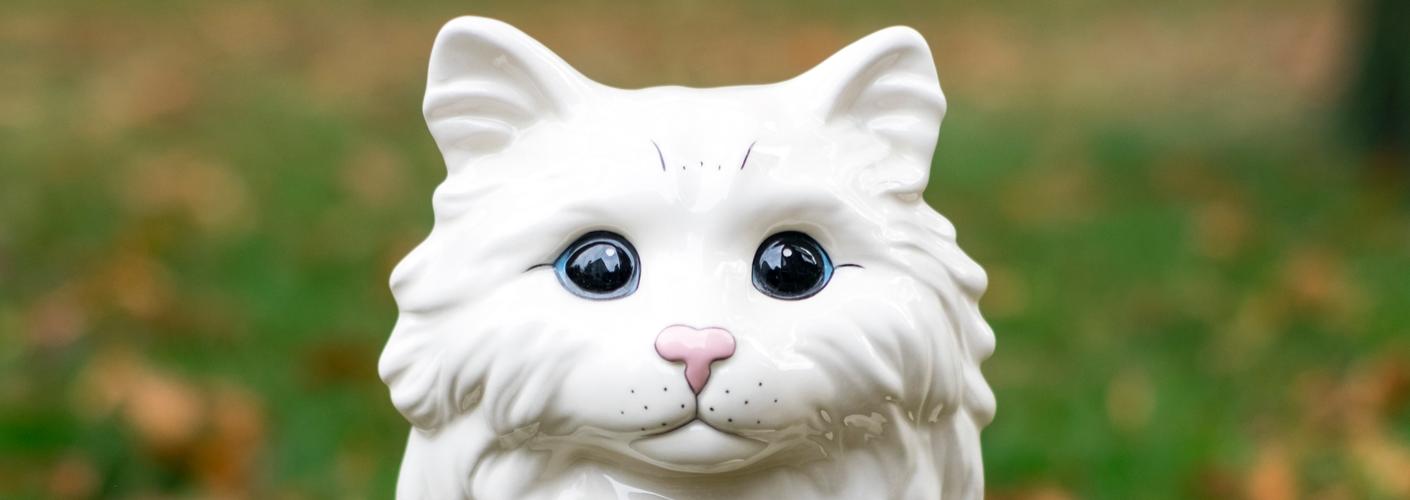 Auf dem Foto ist ein weißer Katzenkof aus Porzellan zu sehen. Es ist der Flyer zu der Ausstellung in der Galerie Affenfaust
