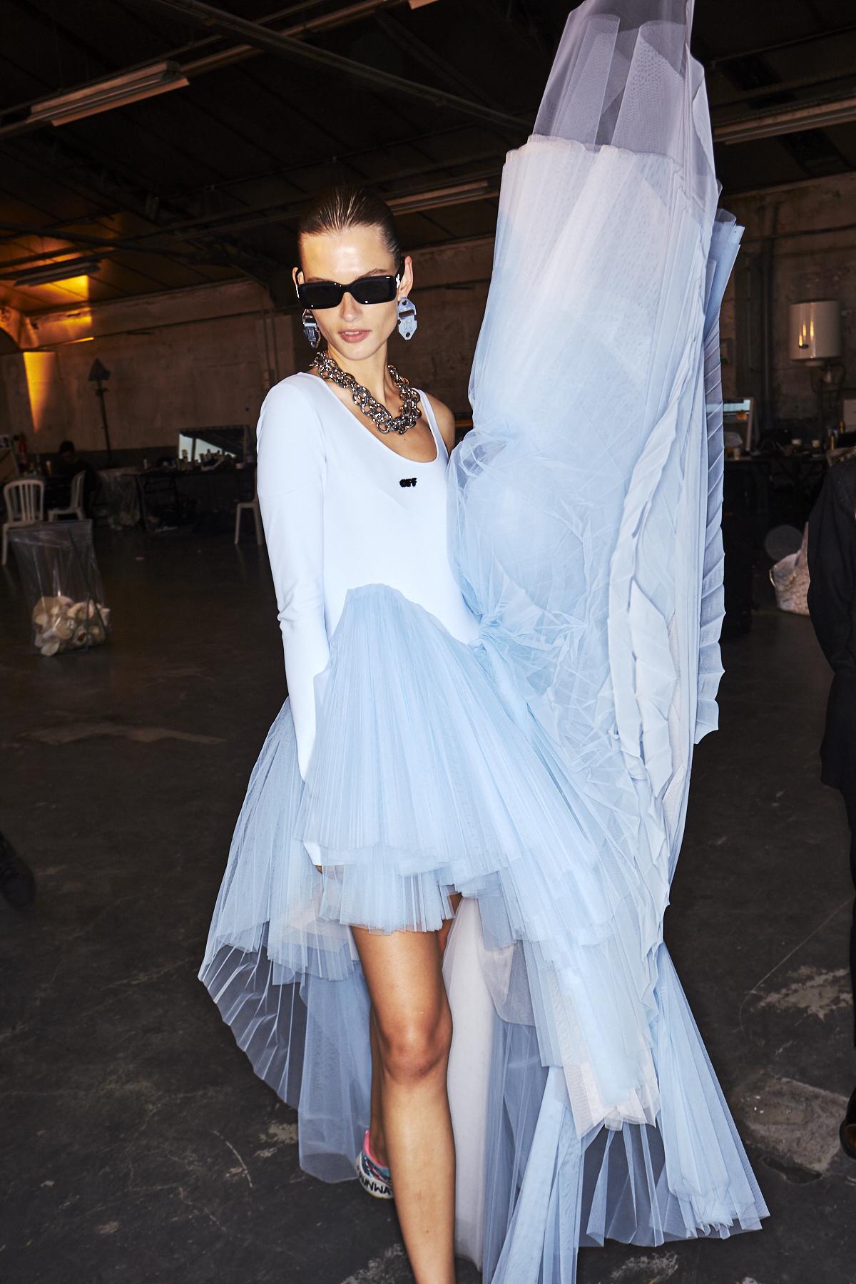 Dieses Model im Backstage-Bereich der Off-White Frühjahr/Sommer Show trägt ein hellblaues Kleid mit Plisseerock aus Tüll.