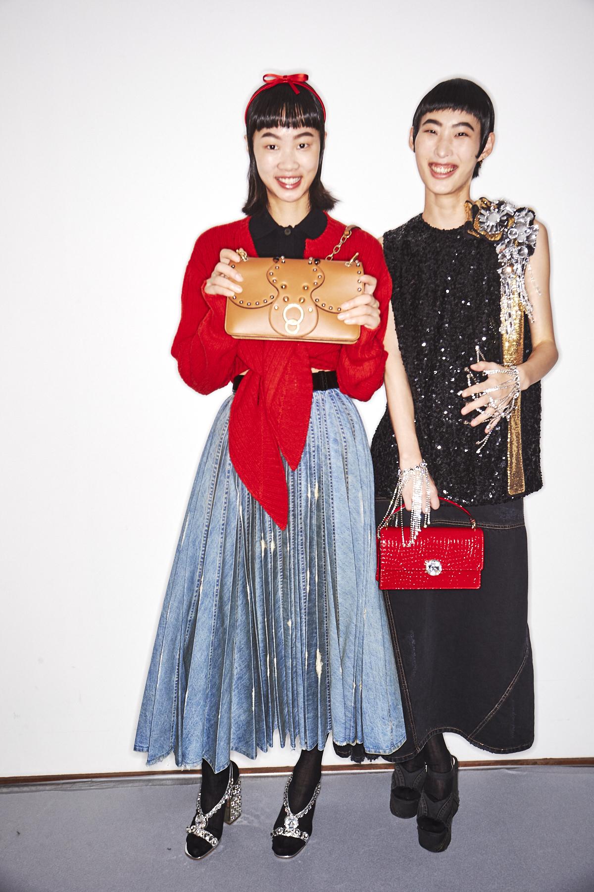 Auf diesem Bild sind zwei Mädchen im Backstage-Bereich der Miu Miu Frühjahr/Sommer 2019 Show. Eines trägt einen wadenlangen Plisseerock aus Jeans.