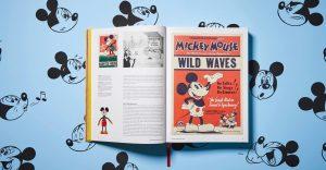 Auf diesem Foto ist das aufgeschlagene Buch: Walt Disneys Mickey Mouse - Die ultimative Chronik zu sehen. Es ist im Taschen Verlag erschienen. Auf dem hellblauen Hintergrund sieht man schwarz gezeichnete Mickey Mouse Köpfe.
