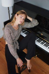 Auf dem Foto ist die Influencerin Hannah Pot d`Or am Klavier sitzend zu sehen.