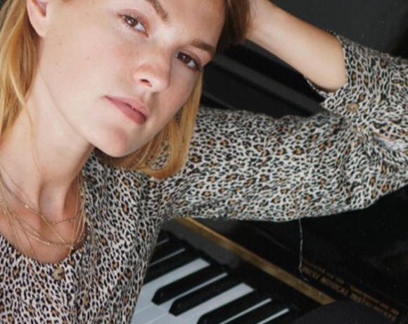 Auf dem Foto ist die Infuencerin Hannah Pot d`Or am Klavier sitzend zu sehen.